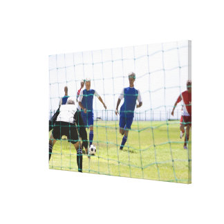mature men kicking soccer ball towards stretched canvas print