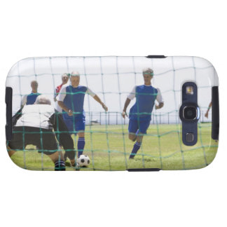 mature men kicking soccer ball towards galaxy s3 covers