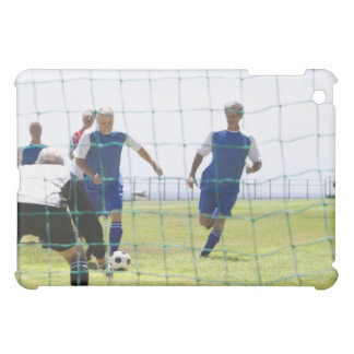 mature men kicking soccer ball towards iPad mini cover
