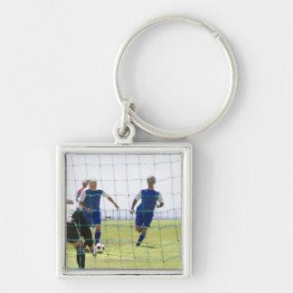 mature men kicking soccer ball towards Silver-Colored square key ring