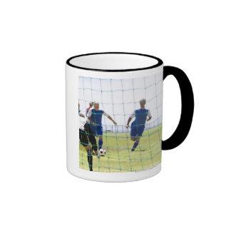 mature men kicking soccer ball towards coffee mugs