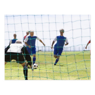 mature men kicking soccer ball towards postcard