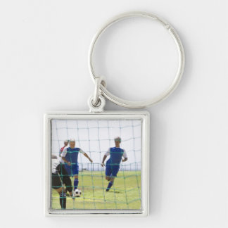 mature men kicking soccer ball towards Silver-Colored square key ring