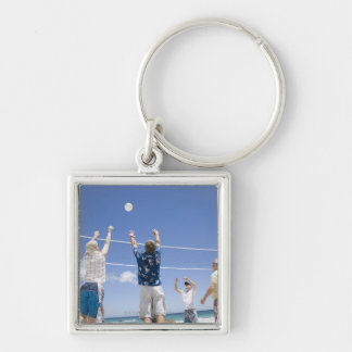 Mature men leaping for volley ball on beach, key ring