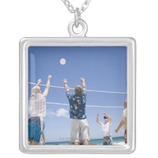 Mature men leaping for volley ball on beach, silver plated necklace