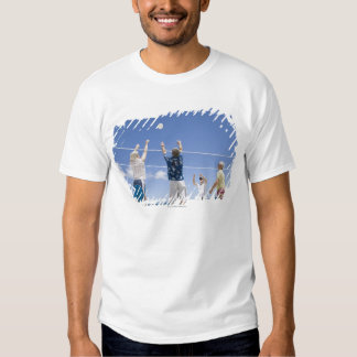 Mature men leaping for volley ball on beach, t shirt