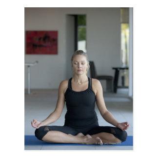 Mature woman practicing yoga postcard