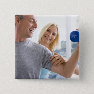 Mature woman smiling at mature man lifting 15 cm square badge