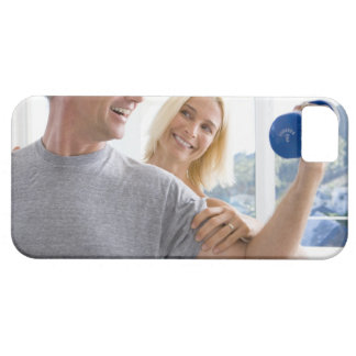 Mature woman smiling at mature man lifting case for the iPhone 5