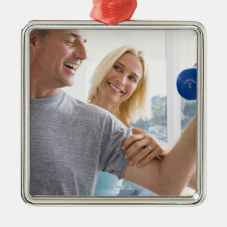 Mature woman smiling at mature man lifting Silver-Colored square decoration