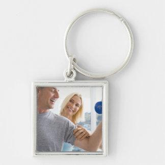 Mature woman smiling at mature man lifting Silver-Colored square key ring