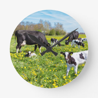 Meadow full of dandelions with grazing cows wallclocks
