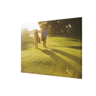 Men carrying golf bags on golf course canvas print