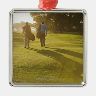 Men carrying golf bags on golf course christmas ornament