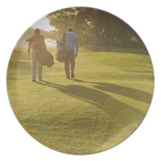 Men carrying golf bags on golf course plate