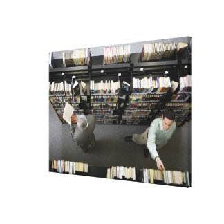 Men in library looking for books canvas print