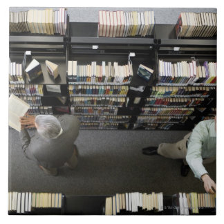 Men in library looking for books tile