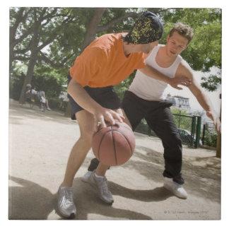 Men playing basketball outdoors tile