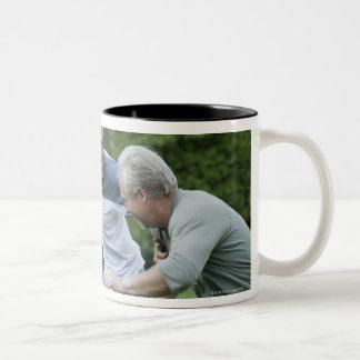 Men playing football coffee mug