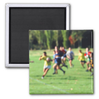 Men playing in park, defocused magnet