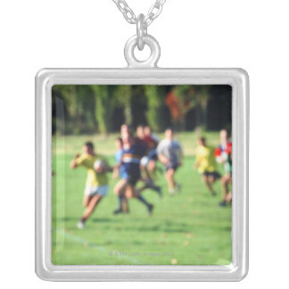 Men playing in park, defocused silver plated necklace