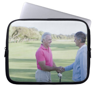 Men shaking hands on golf course computer sleeves
