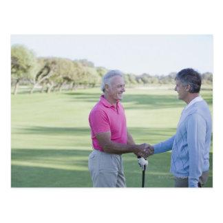 Men shaking hands on golf course postcard