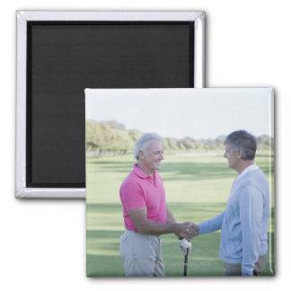 Men shaking hands on golf course square magnet