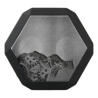 Metal background with mechanical damage black bluetooth speaker