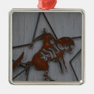 Metal sculpture of cowboy on bucking bronco christmas ornament