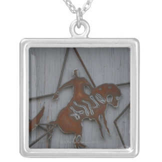 Metal sculpture of cowboy on bucking bronco square pendant necklace
