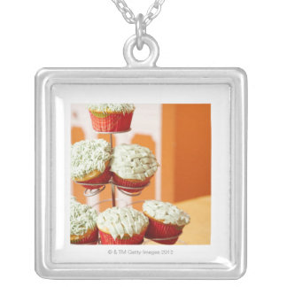 Metal tree displaying frosted cupcakes silver plated necklace