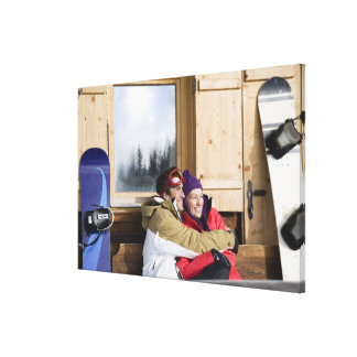 Mid adult couple embracing outside log cabin canvas print