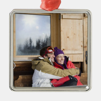 Mid adult couple embracing outside log cabin christmas ornament
