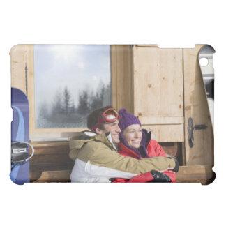 Mid adult couple embracing outside log cabin iPad mini cover