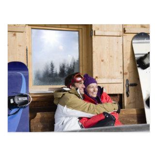 Mid adult couple embracing outside log cabin postcard
