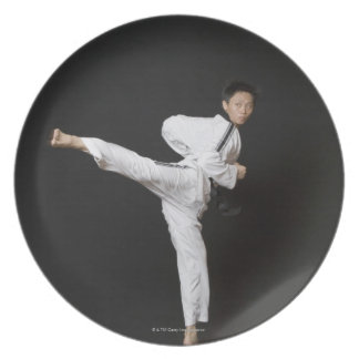Mid adult man performing the side kick plate