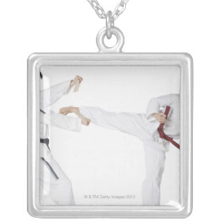 Mid adult man practicing kickboxing with a young silver plated necklace