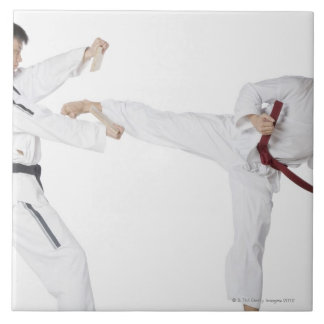 Mid adult man practicing kickboxing with a young tile