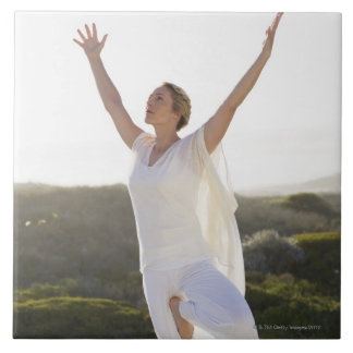 Mid adult woman practicing yoga 2 tile