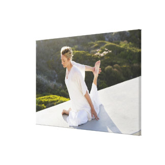 Mid adult woman practicing yoga exercise at canvas print
