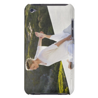 Mid adult woman practicing yoga exercise at iPod touch case