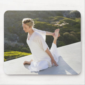 Mid adult woman practicing yoga exercise at mouse mat