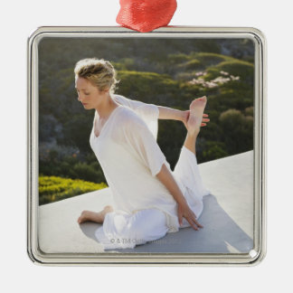 Mid adult woman practicing yoga exercise at Silver-Colored square decoration