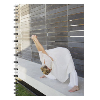 Mid adult woman stretching her arms notebooks