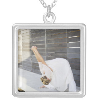 Mid adult woman stretching her arms silver plated necklace