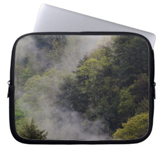 Mist rising from mountainside after spring rain, laptop sleeve