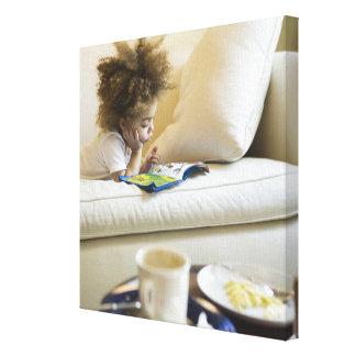 Mixed race boy reading book on sofa canvas print