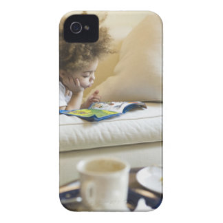 Mixed race boy reading book on sofa iPhone 4 cases