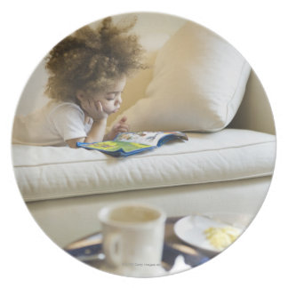 Mixed race boy reading book on sofa plate
